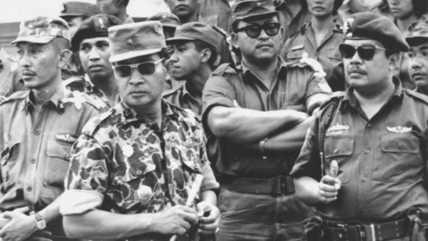 ndonesia's Major-General Suharto, in camouflage uniform, at the funeral for
